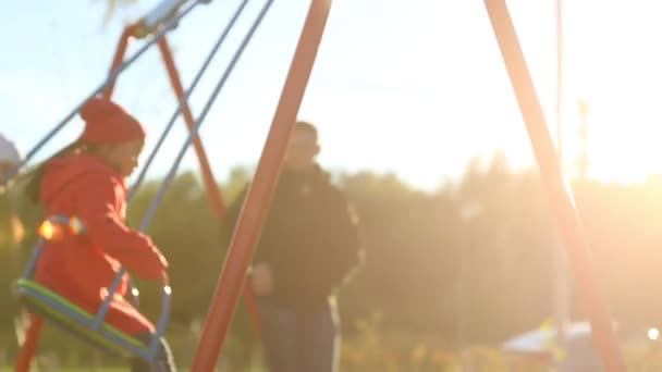 Zwei Mädchen schwingen auf Schaukel im sonnigen Tag auf Kinderspielplatz