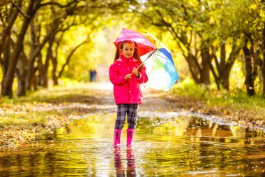 Adorable toddler girl with colorful umbrella outdoors at autumn rainy day
