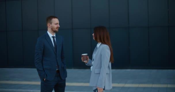 Arbeitskollegen im Business-Stil stehen in der Nähe eines modernen Gebäudes, trinken Kaffee und diskutieren über Arbeitsthemen..
