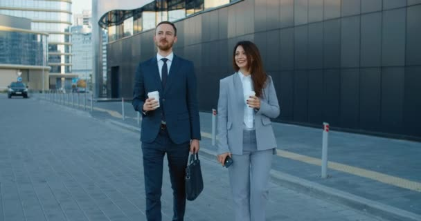 Work colleagues man and woman in business style are walking near a modern building, drinking coffee and discussing work topics.