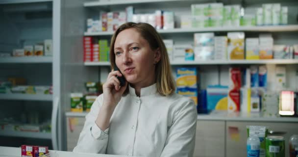 A pharmacist woman stands in a pharmacy against the background of drugs and talks on the phone. Working conversations. Female portrait