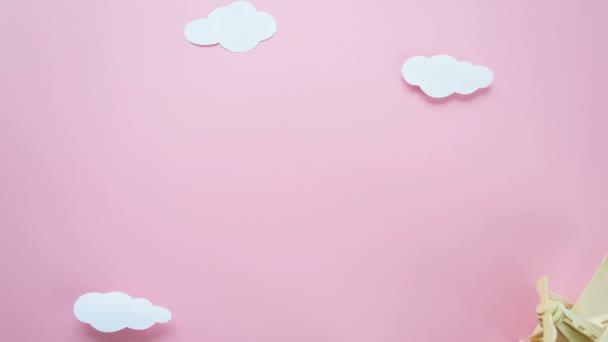Šťastný Valentines den. Ekologické dřevěné dětské letadlo na růžovém pozadí s červeným srdcem a girlanda ve tvaru srdce bílé mraky, příznaky. Stop motion animace smyčka.