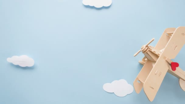 Happy Valentines day. Eco wooden childrens plane on a blue background with red heart, and garland in the shape of a heart white clouds, flags. Stop motion animation loop.