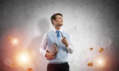 horizontale Aufnahme eines selbstbewussten und jungen Geschäftsmannes in Smart-Casual-Kleidung, der Pfeife raucht, während er zwischen fliegenden Glühbirnen und vor grauer dunkler Wand im Hintergrund steht.