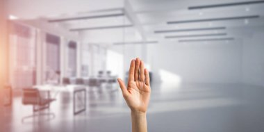 Close of woman hand touching screen with palm and office at background