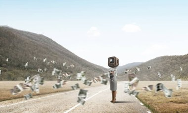 Business woman in suit with old TV instead of head keeping arms crossed while standing on the road among flying dollar banknotes with beautiful landscape on background.