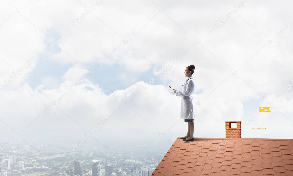 Conceptual image of professional woman doctor in white medical uniform holding tablet in hands while standing on brick roof with skyscape and city view on background.