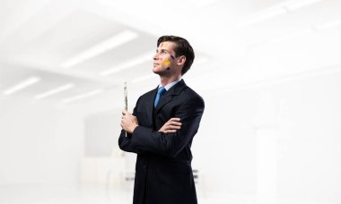 Portrait of young thoughtful man holding paintbrush in his hand and looking away while standing inside modern office view on background.