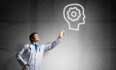 Confident doctor in white uniform interracting with glowing gear brain symbol while standing against gray dark wall on background.