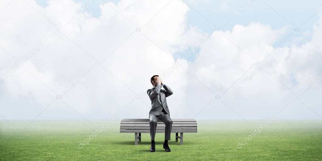 Young shocked businessman sitting on wooden bench and covering eyes with palms