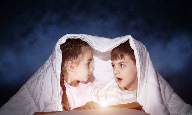 Scared little girl and boy looking at each other under blanket. Children together reading magic stories in bed before going to sleep. Young sister and brother in pajamas on deep blue sky background