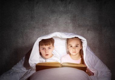 Frightened girl and boy looking at each other under blanket. Children reading magic stories in bed before going to sleep. Young sister and brother in pajamas together on background of grey wall.