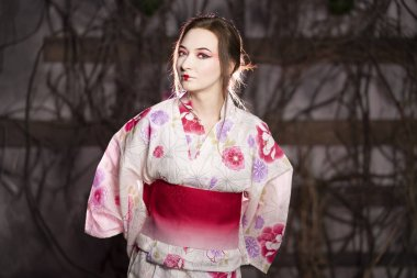 elegant girl in a classic traditional dress Japanese kimono white and pink standing alone on dark background in the studio