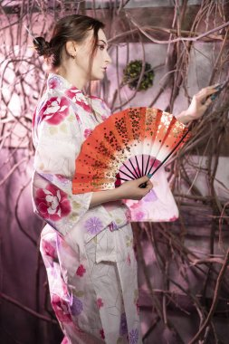 beautiful fair-skinned girl with Japanese makeup and Japanese clothes standing with a red fan near the tree branches and window