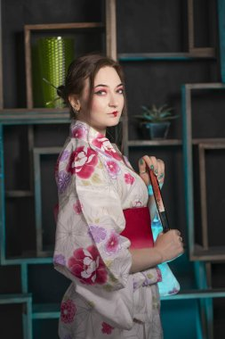 beautiful young woman standing at night in her room and posing in Japanese kimono alone