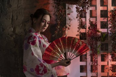beautiful young woman standing at night in her garden and posing in Japanese kimono alone