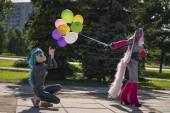 Fotografie lustig-Freaks, gekleidet in einen hellen Kostüm Einhorn und Anime Gesichtsmaske mit Latex Catsuit, genießen Sie das Leben in der Stadt Park