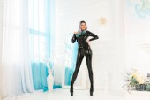 Fotografie luxury fashionable girl dressed in black catwoman costume posing in her white room at home alone
