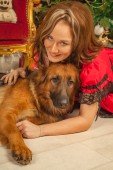 Photo  beautiful girl in a red fabulous dress posing with her shepherd big dog and delicious pies in her beige room on the background of a Christmas tree