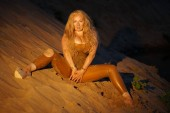 Fotografie beautiful girl in latex soiled in the sand on the beach at the night