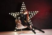 heißen kaukasischen Frau posiert in erotischen Latex Rubber versauten Kostüm allein in der Nähe der Beleuchtung-star