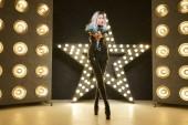 stylische High-Fashion-Frau posiert in schwarzer Kleidung im Studio mit Glühbirnen