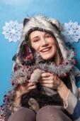 Szép nő a szőr téli kalap tartó kis aranyos Pásztor kiskutya és mosolygó kék háttér
