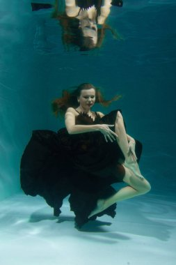 beautiful lady in long evening dress swimming underwater on the deep alone