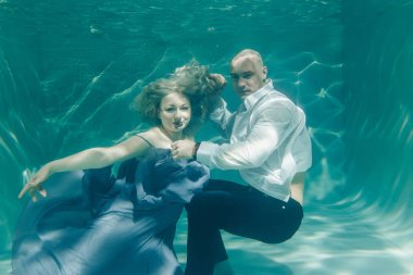 beautiful romantic couple of lovers hugging gently under water