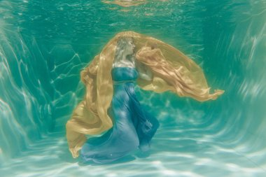 chubby sexy woman in grey evening long dress swimming underwater on her holidays and enjoy with relax