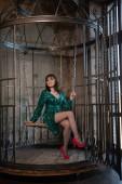 schöne Frau, die allein in einem Käfig sitzt, aufgrund ihrer Einschränkungen und Komplexe. erwachsenes Weibchen im grünen Abendkleid im eisernen großen Käfig.