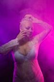 Mollige sexy Frau trägt weiße sexy Spitzenkleid und Dessous im Rauch