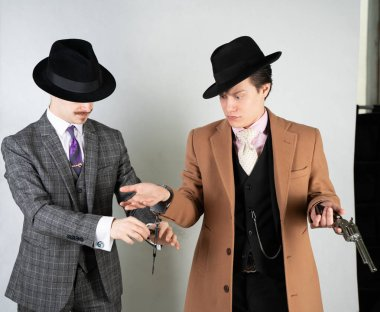 two friends dressed in vintage clothes and depict retro detectives and spies in English classic style on a white studio background