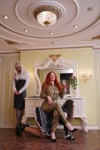 Strict redhead mistress in leopard latex rubber catsuit trains her two fetish slaves who are disguised as women and ready to serve submissively. domina, secretary and maid crossdressers into bedroom. luxury orgy