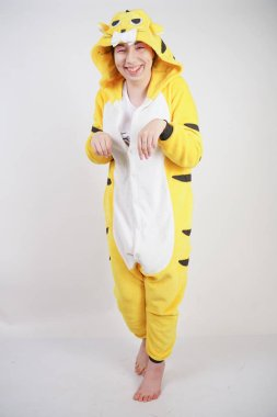 funny cheerful girl in big yellow pajamas kigurumi posing on a white background in the Studio