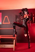 sexueller erwachsener Junge in schwarzem Latex-Gummi-Catsuit mit Fetisch-Korsett und flauschigen Katzenohren mit roter Nackenschleife posiert im BDSM-Raum