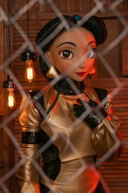 beautiful girl with full face mask doll in leather space jumpsuit posing in her room with light bulbs alone
