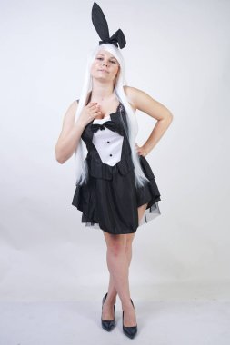 cute girl with long white hair with Bunny ears in rabbit costume on white background in Studio. a woman with a plus size body stands and do fashion poses in a black dress.