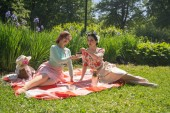 two pretty pin up ladies having nice picnic in the city park in a sunny day together. girls friends enjoy hot summer weather. beautiful females in retro vintage style are relaxing on the grass.