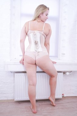 pretty plus size woman wearing beige tight corset and fashion bra with panties