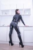 schöne Frau im Latex-Anzug auf weißem Küchenhintergrund