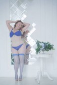 pretty chubby woman in fashion blue lingerie in her white room indoors alone