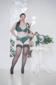 happy plus size mix race woman posing in fashion lingerie and stockings indoors in white apartment alone