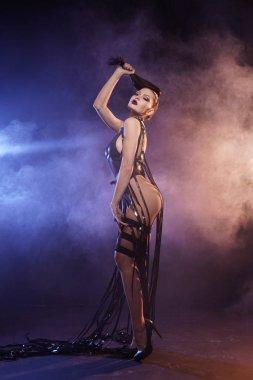 Young sexy woman dancer posing in the smoke