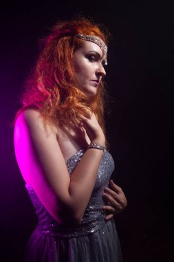 Mature plus size red hair woman in grey evening dress posing on dark smoke background ready for halloween.