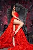 Fotografie schöne Vampirfrau im roten langen Kleid in der Nähe des großen schwarzen Throns im Atelier