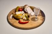 Orosz csendélet: egy izzadt pohár jeges orosz vodka, hagyományos népi snack: Sertészsír, Ecetes uborka, forró piros paprika, hagyma és fokhagyma - egy fából készült hajón. Ünnep titokzatos orosz lélek