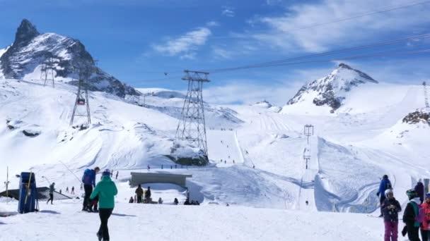 Skiers skiing at the ski track on the Klein Matterhorn ski resort in sunny day at Zermatt Village in Switzerland