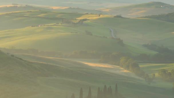 Toskánsko, Itálie - 10 června 2018: Pohled kopcovité toskánské louce farmu a cypřiše v zlaté večerní hodinu při Valdocia ve střední Itálii