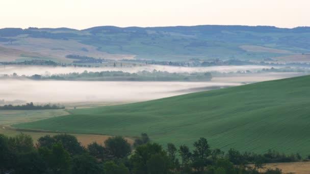 Blick auf die hügelige Landschaft der Toskana am Morgen mit Nebel auf dem Boden, die Zypressen und das Gebäude in der Toskana Italien